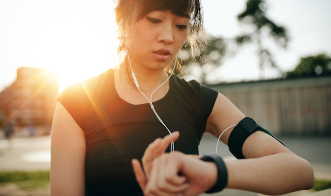 Woman using her fitness tracker while exercising; wearable technology
