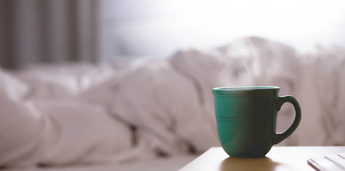 Coffee cup next to a bed