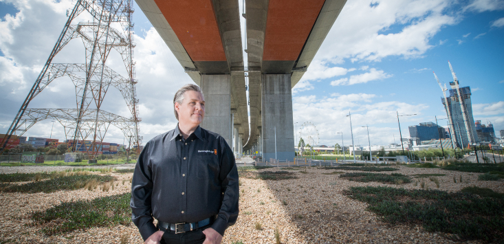 Grant Petty, Blackmagic Design founder standing under bridge looking into the distance